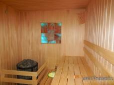 Сауна с электрической печью и соляной панелью на стене.